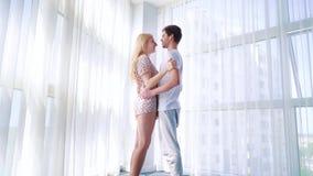 Ζουμ μέσα των νέων εραστών στις πυτζάμες που αγκαλιάζουν στην ηλιοφάνεια πρωινού κοντά στο μεγάλο παράθυρο απόθεμα βίντεο
