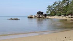 Ζουμ σε έναν βράχο και μικρά κύματα που έρχονται στην παραλία απόθεμα βίντεο