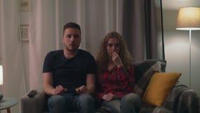 Ζουμ στον πυροβολισμό του καθιστικού ζευγών που προσέχει αργά τη νύχτα μια τρομακτική ταινία φρίκης απόθεμα βίντεο