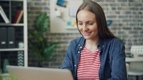 Ζουμ στο πορτρέτο της όμορφης νέας κυρίας που χρησιμοποιεί το lap-top στην εργασία που χαμογελά έπειτα απόθεμα βίντεο