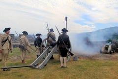Ζοφερή άποψη των νεαρών άνδρων που βάζουν φωτιά στους κανόνες κατά τη διάρκεια των πολεμικών αναπαραστάσεων, οχυρό Ticonderoga, Ν Στοκ Εικόνες