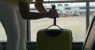 Ζυγίζοντας αποσκευές γυναικών με τις κλίμακες χεριών φιλμ μικρού μήκους