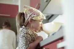 Ζυγίζοντας αλεύρι μικρών κοριτσιών για ένα κέικ γενεθλίων στοκ εικόνα