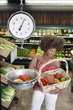 Ζυγίζοντας πιπέρια κουδουνιών γυναικών αφροαμερικάνων στην κλίμακα στην υπεραγορά Στοκ Εικόνες