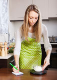 Ζυγίζοντας τυρί εξοχικών σπιτιών γυναικών στις κλίμακες κουζινών Στοκ Εικόνες