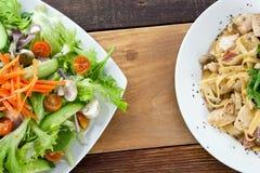 Ζυμαρικά και σαλάτα στον ξύλινο πίνακα Στοκ Εικόνες