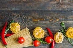 Ζυμαρικά με την ντομάτα, πιπέρια τσίλι, δεντρολίβανο στον ξύλινο πίνακα Στοκ εικόνες με δικαίωμα ελεύθερης χρήσης