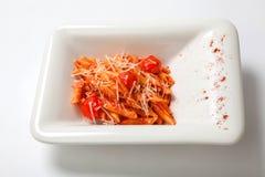 Ζυμαρικά με τη σάλτσα ντοματών που ψεκάζεται με το τυρί παρμεζάνας στοκ εικόνα