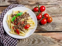 Ζυμαρικά με τις ντομάτες και κρέας στο ξύλινο υπόβαθρο Στοκ Εικόνες
