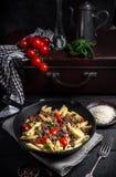 Ζυμαρικά με τις ντομάτες και κρέας στο σκοτεινό αγροτικό υπόβαθρο Στοκ φωτογραφία με δικαίωμα ελεύθερης χρήσης