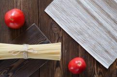 Ζυμαρικά με τις ντομάτες στον ξύλινο πίνακα Στοκ Εικόνες