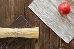 Ζυμαρικά με τις ντομάτες στον ξύλινο πίνακα Στοκ Φωτογραφίες
