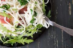 Ζυμαρικά με το λαχανικό prosciutto και arugula σε ένα πιάτο Στοκ Εικόνες