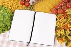 Ζυμαρικά με το κενό βιβλίο συνταγής και τον τεμαχίζοντας πίνακα στοκ φωτογραφίες