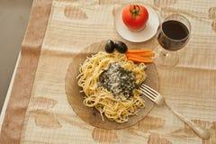 Ζυμαρικά με το pesto σάλτσας, τις μαύρες ελιές, την ντομάτα και το κρασί Στοκ Εικόνες