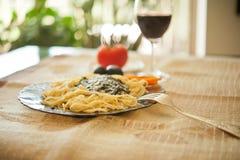 Ζυμαρικά με το pesto σάλτσας, το τυρί παρμεζάνας, τις μαύρες ελιές και ένα gla Στοκ εικόνα με δικαίωμα ελεύθερης χρήσης