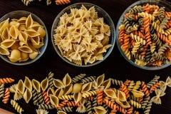 Ζυμαρικά στο σκοτεινό ξύλινο υπόβαθρο στη μακροεντολή κινηματογραφήσεων σε πρώτο πλάνο πιάτων γυαλιού Στοκ Εικόνες