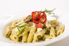 Ζυμαρικά της Penne με το τυρί φέτα, το σπανάκι, το pesto και το ξηραμένο από τον ήλιο tomat στοκ φωτογραφίες