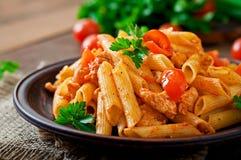 Ζυμαρικά της Penne στη σάλτσα ντοματών με το κοτόπουλο, ντομάτες που διακοσμούνται με το μαϊντανό Στοκ Εικόνες