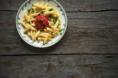 Ζυμαρικά της Penne στη σάλτσα ντοματών, ντομάτες που διακοσμούνται με το μαϊντανό σε ένα ξύλινο υπόβαθρο Στοκ Εικόνες