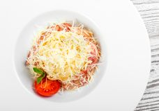 Ζυμαρικά Fettuccine με το κρέας, το ζαμπόν, το τυρί παρμεζάνας, το βασιλικό και την ντομάτα στο πιάτο στο ελαφρύ ξύλινο υπόβαθρο στοκ εικόνα με δικαίωμα ελεύθερης χρήσης