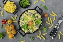 Ζυμαρικά Fusilli με το σπανάκι, κεράσι, μπέϊκον στα μαύρα πιάτα στοκ φωτογραφία