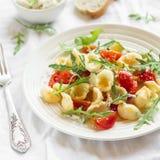 Ζυμαρικά Orecchiette με τις ντομάτες κερασιών, το arugula και το τυρί παρμεζάνας σε ένα άσπρο πιάτο Στοκ Εικόνες