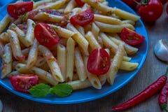 Ζυμαρικά penne με τις ντομάτες και τα τσίλι πιπεριών Στοκ Εικόνες