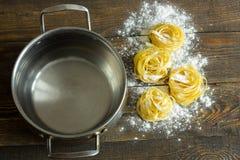 Ζυμαρικά tagliatelle με το αλεύρι στον πίνακα και το τηγάνι Στοκ Εικόνα