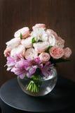 1 ζωή ακόμα ένας ξύλινος παλαιός πίνακας, βάζο γυαλιού με τη μικτή ανθοδέσμη όμορφα λουλούδια Στοκ Φωτογραφία