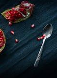 1 ζωή ακόμα ασημένιο κουτάλι, ρόδι περικοπών και σιτάρια γρανατών σε ένα σκοτεινό υπόβαθρο Στοκ Εικόνες