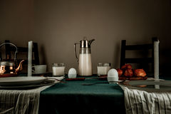 1 ζωή ακόμα γεύμα αγροτικό κανάτα γάλακτος, κεριά, τσάι, αυγά, ρόλοι ψωμιού στον πίνακα Στοκ Εικόνα