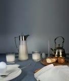 1 ζωή ακόμα γεύμα αγροτικό κανάτα γάλακτος, κεριά, τσάι, αυγά, ρόλοι ψωμιού στον πίνακα Στοκ Φωτογραφία
