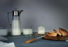 1 ζωή ακόμα γεύμα αγροτικό κανάτα γάλακτος, κεριά, τσάι, αυγά, ψωμί, ρόλοι, τυρί, στον πίνακα Στοκ εικόνες με δικαίωμα ελεύθερης χρήσης