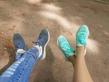 1 ζωή ακόμα Διασχισμένος ο ένας με τον άλλον δύο ζευγάρια των ποδιών στους στιλίστες Ένα ζευγάρι των ποδιών στα μπλε σχισμένα τζι Στοκ φωτογραφίες με δικαίωμα ελεύθερης χρήσης
