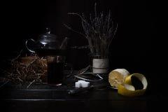 1 ζωή ακόμα η ανθοδέσμη lavender, κατσαρόλα τσαγιού, φλυτζάνια, ξεφλούδισε το λεμόνι σε έναν ξύλινο πίνακα Μαύρη ανασκόπηση Στοκ εικόνα με δικαίωμα ελεύθερης χρήσης