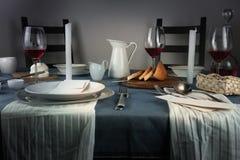 1 ζωή ακόμα η κανάτα, αυξήθηκε κρασί στα γυαλιά, κουλούρι, άσπρα κεριά σε ένα μπλε τραπεζομάντιλο Στοκ Εικόνες