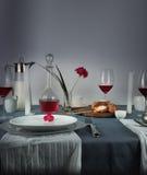 1 ζωή ακόμα η κανάτα του γάλακτος, αυξήθηκε κρασί στα γυαλιά, κουλούρι, άσπρα κεριά σε ένα μπλε τραπεζομάντιλο Στοκ Εικόνες