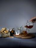 1 ζωή ακόμα Θηλυκό χύνοντας τσάι χεριών από teapot στο φλυτζάνι γυαλιού Στοκ Εικόνα