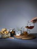 1 ζωή ακόμα Θηλυκό χύνοντας τσάι χεριών από teapot στο φλυτζάνι γυαλιού Στοκ φωτογραφία με δικαίωμα ελεύθερης χρήσης