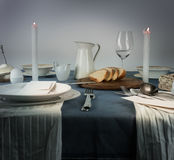 1 ζωή ακόμα κανάτα, γυαλιά, κουλούρι, άσπρα κεριά σε ένα μπλε τραπεζομάντιλο Στοκ Φωτογραφίες