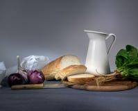 1 ζωή ακόμα κανάτα, κουλούρι, κρεμμύδι, σκόρδο, σπανάκι σε ένα μπλε τραπεζομάντιλο Στοκ Εικόνες