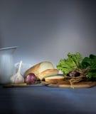 1 ζωή ακόμα κανάτα, ψωμί, κρεμμύδι, σκόρδο, σπανάκι σε ένα μπλε τραπεζομάντιλο Διάστημα για το κείμενο Στοκ Εικόνες