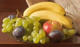 1 ζωή ακόμα Πιατέλα φρούτων: μπανάνες, σταφύλια, Apple, δαμάσκηνα Στοκ Φωτογραφία