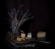 1 ζωή ακόμα σκληρό τυρί, μια δέσμη lavender, παλαιό ασημένιο μαχαίρι στον ξύλινο πίνακα Μαύρη ανασκόπηση Στοκ Εικόνες