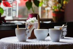1 ζωή ακόμα Τα άσπρα φλυτζάνια πορσελάνης και ένα βάζο των λουλουδιών στέκονται σε έναν πίνακα με ένα άσπρο τραπεζομάντιλο σε μια Στοκ Φωτογραφία