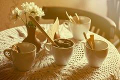 1 ζωή ακόμα Τα άσπρα φλυτζάνια πορσελάνης και ένα βάζο των λουλουδιών στέκονται σε έναν πίνακα με ένα άσπρο τραπεζομάντιλο σε μια Στοκ Φωτογραφίες