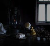 1 ζωή ακόμα Τα μικρά ολλανδικά λαμπτήρας κηροζίνης με το καθαρισμένο λεμόνι και ζάχαρη σε έναν ξύλινο πίνακα ενάντια στο παράθυρο Στοκ Φωτογραφία