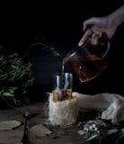 1 ζωή ακόμα τα χέρια χύνουν το τσάι στο διαφανές φλυτζάνι σκοτεινό υπόβαθρο, τρύγος Στοκ εικόνα με δικαίωμα ελεύθερης χρήσης
