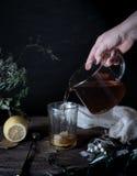 1 ζωή ακόμα τα χέρια χύνουν το τσάι στο διαφανές φλυτζάνι σκοτεινό υπόβαθρο, τρύγος Στοκ Εικόνες